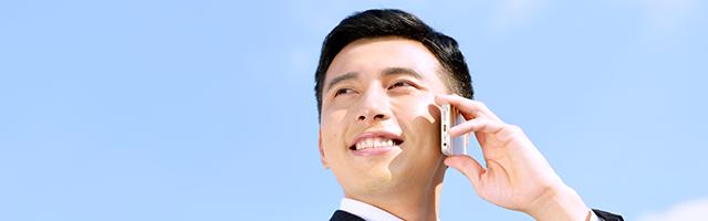 携帯電話で通話する男性の画像