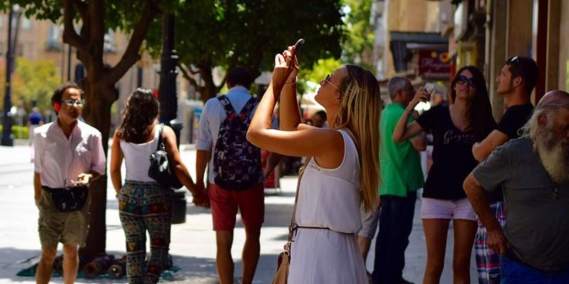 スマートフォンに夢中な人が多く写っている画像